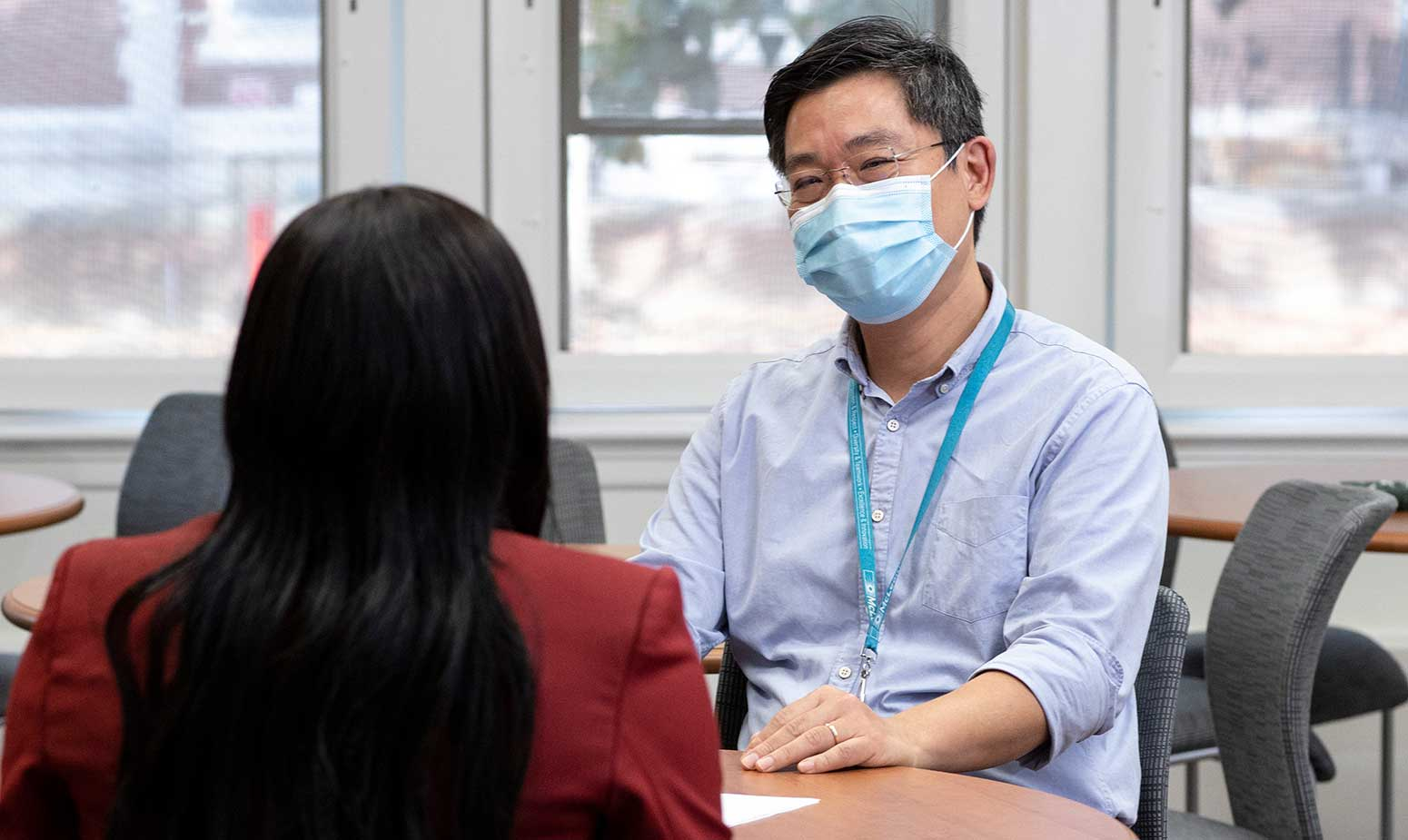 Clinicians in face masks speak, seated at table