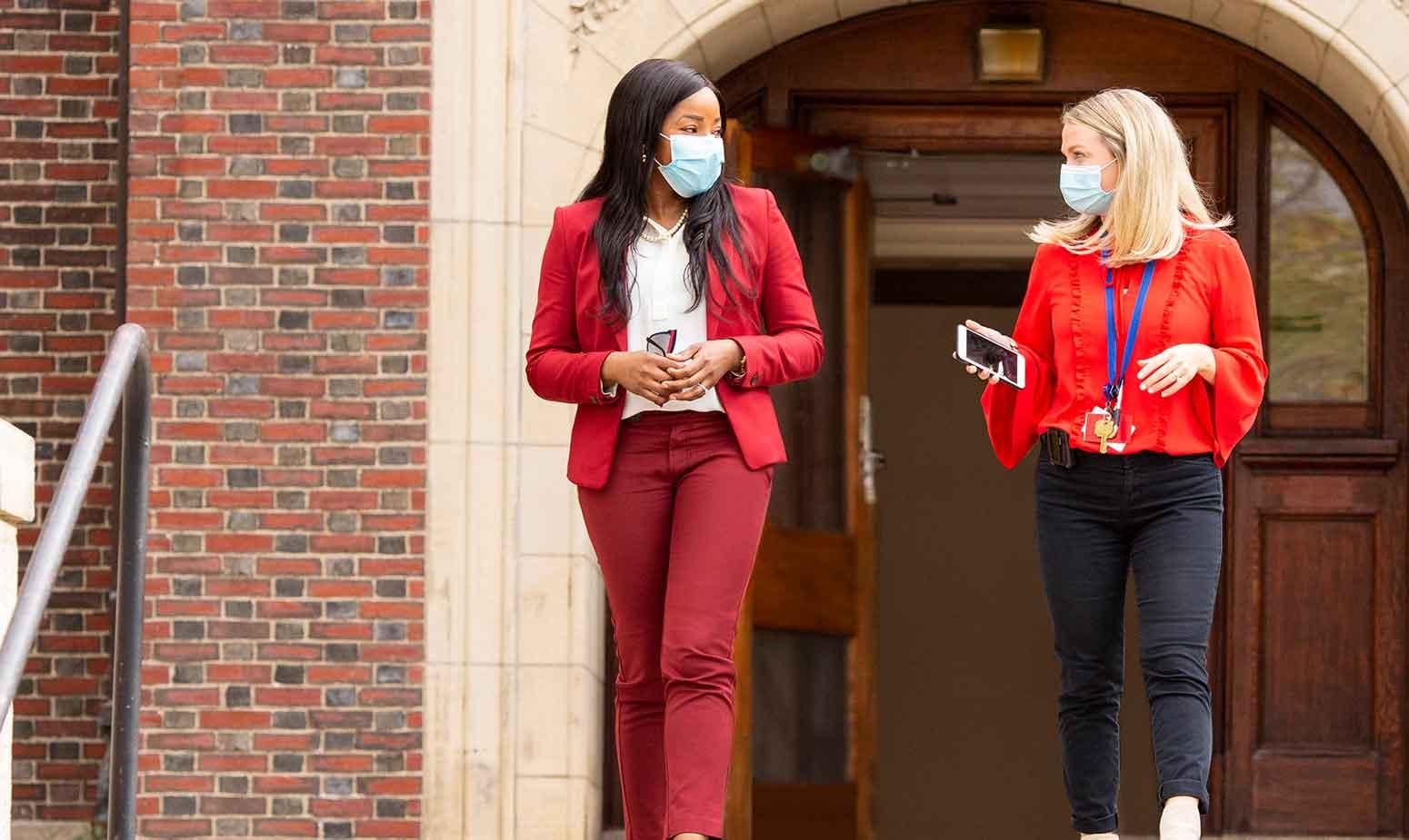 Women walk outside in masks