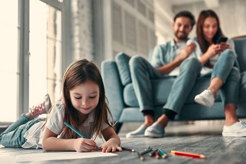 Stock image of man and woman on couch and young girl drawing on floor