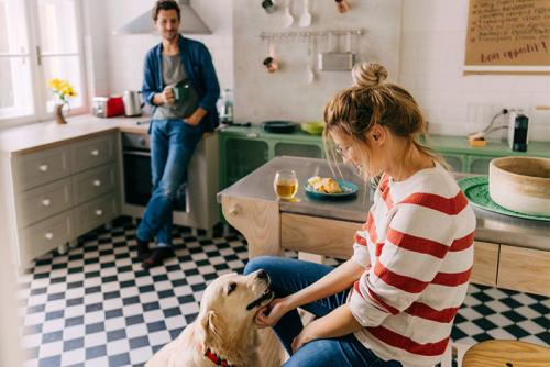 Couple in kitchen with dog