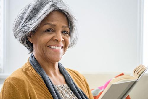 Stock image of woman with book looking at camera