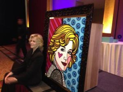 Fonda poses with a portrait painted by Romero Britto