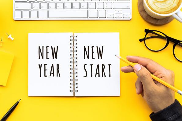 Stock image of notebook with writing new year, new start, desk items on a yellow background