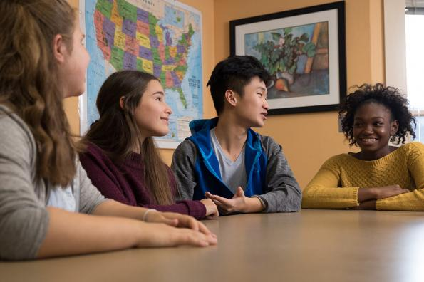 Teens sit at classroom table