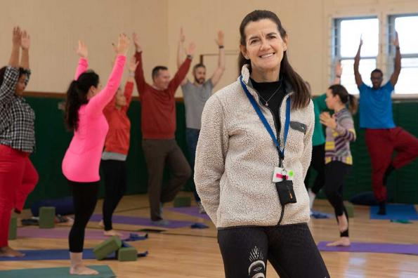 Woman poses in front of yoga class in gym