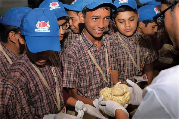 Students in Mumbai looks at a human brain
