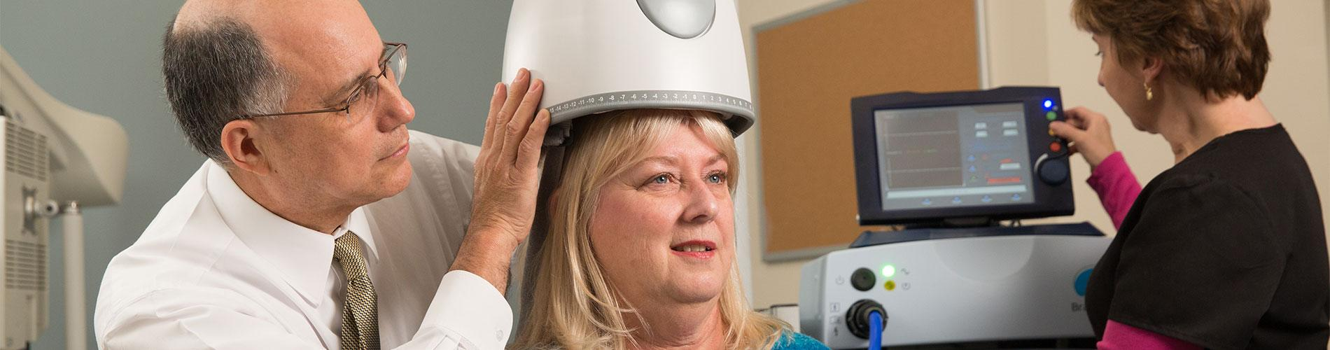Doctor puts TMS helmet on patient as nurse looks at screen