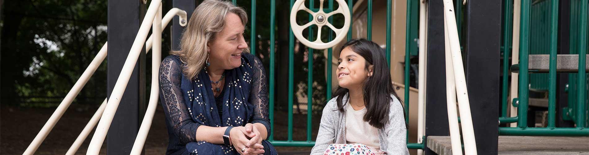 Psychiatrist talks with girl on playground