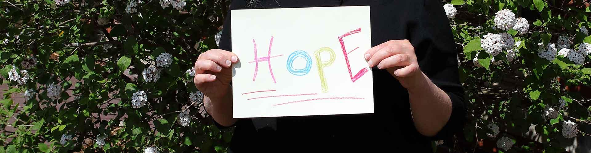 Hands holding up sign with handwritten Hope