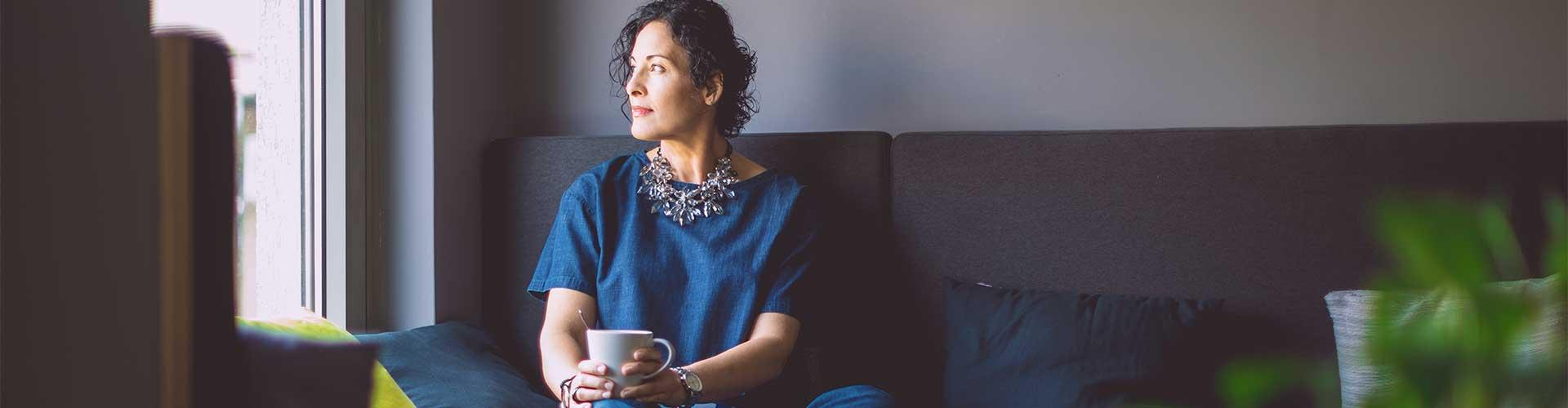 Stock image of woman sitting on couch looking out window