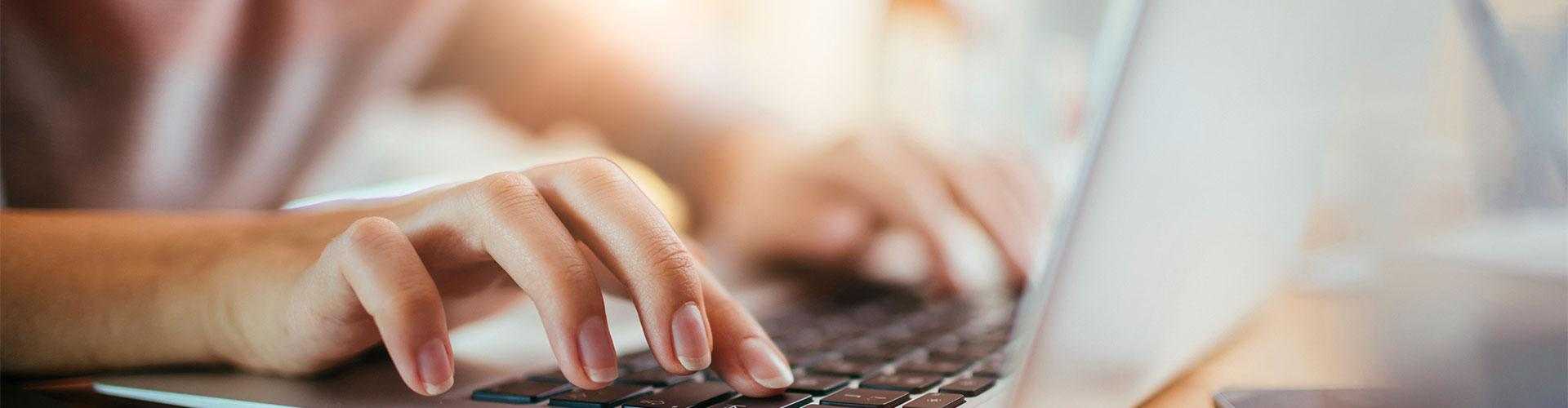 Stock image of hands typing on laptop