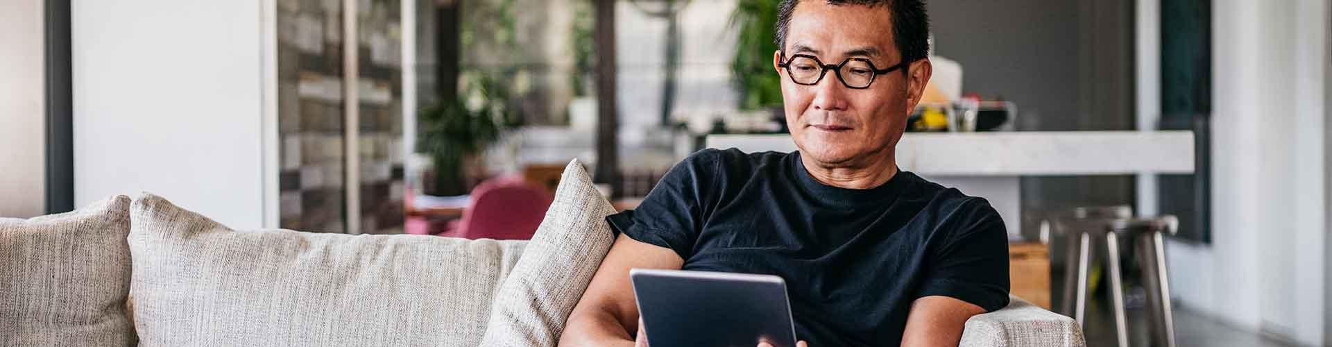 Man sits on couch looking at tablet