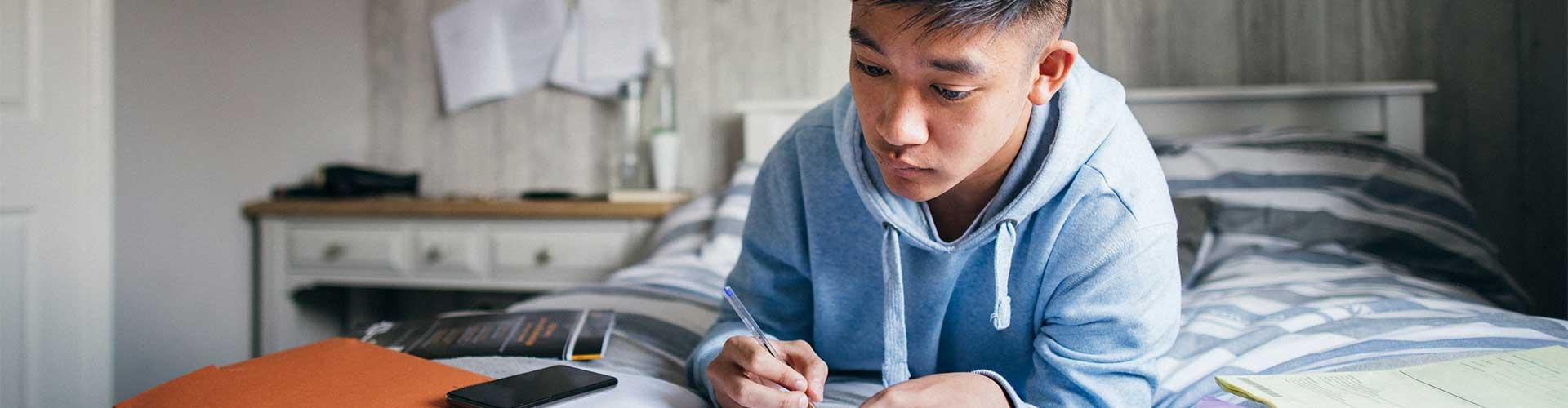 Student does homework on bed