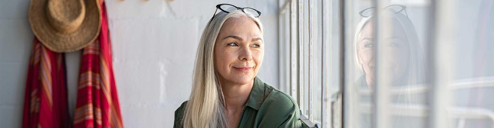Woman with gray hair looks out window