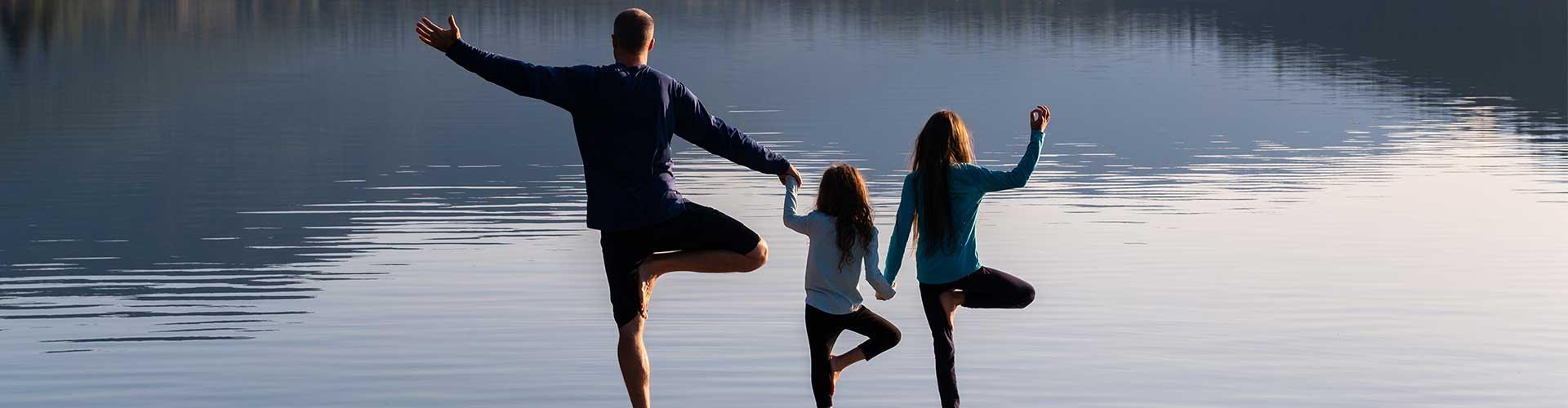 Family doing yoga at end of dock