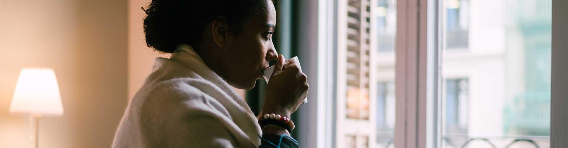 Woman sips coffee looking out window