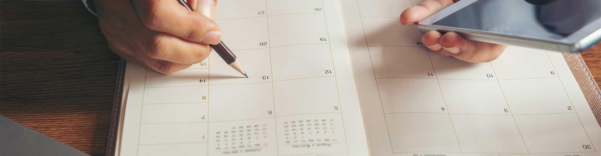 Hands with pencil and smartphone on desk calendar