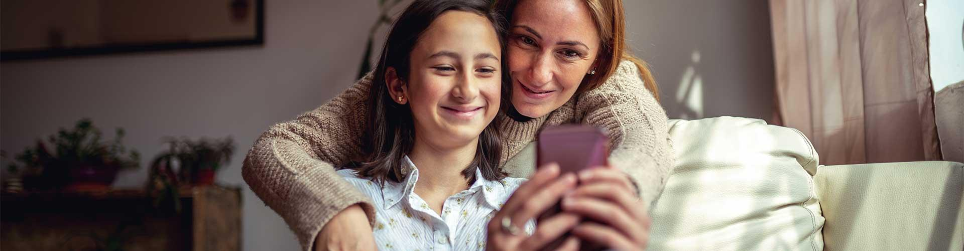 Mom and daughter look at smartphone