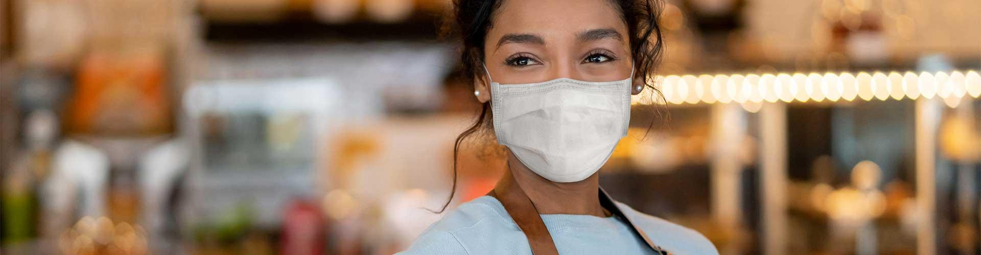 Young woman in mask stands in store