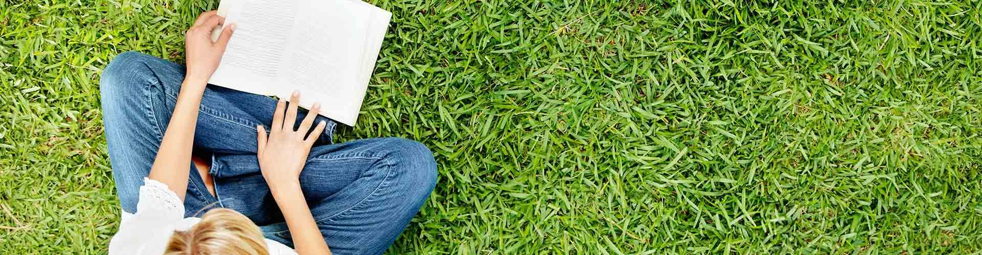 Person reading a book in the grass