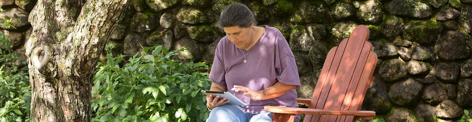Woman sits outside and looks at tablet