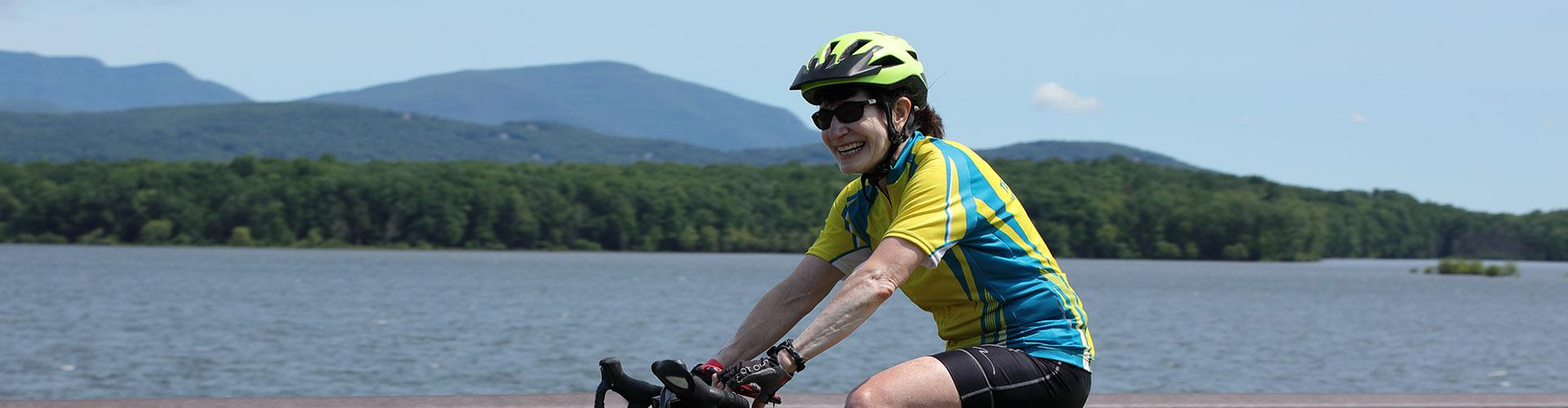 Woman riding bicycle with lake and mountains in background