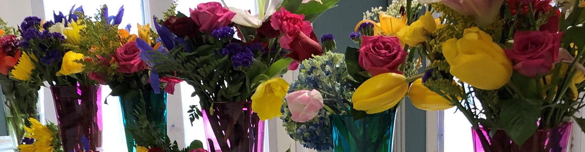 A row of flower arrangements in many colors