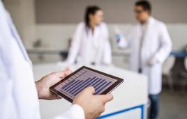 Hand holds tablet with data on it, scientists in background
