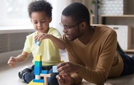Dad and toddler stack blocks