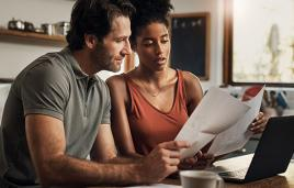 Man and woman look at papers in kitchen