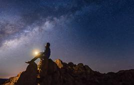 Stock image of man on rock looking at starry sky