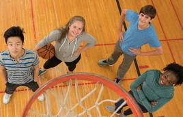 Students stand under basketball hoop