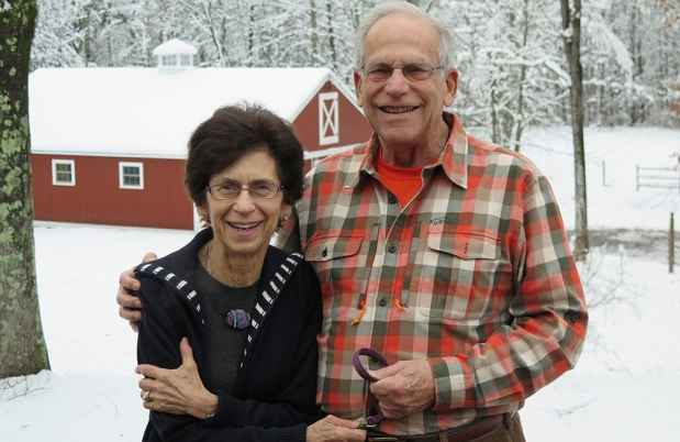 Older couple poses outside in snowy landscape