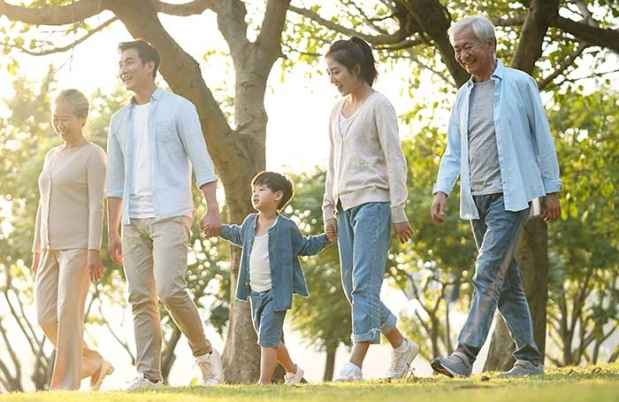 Family walks outside on sunny day with trees in background